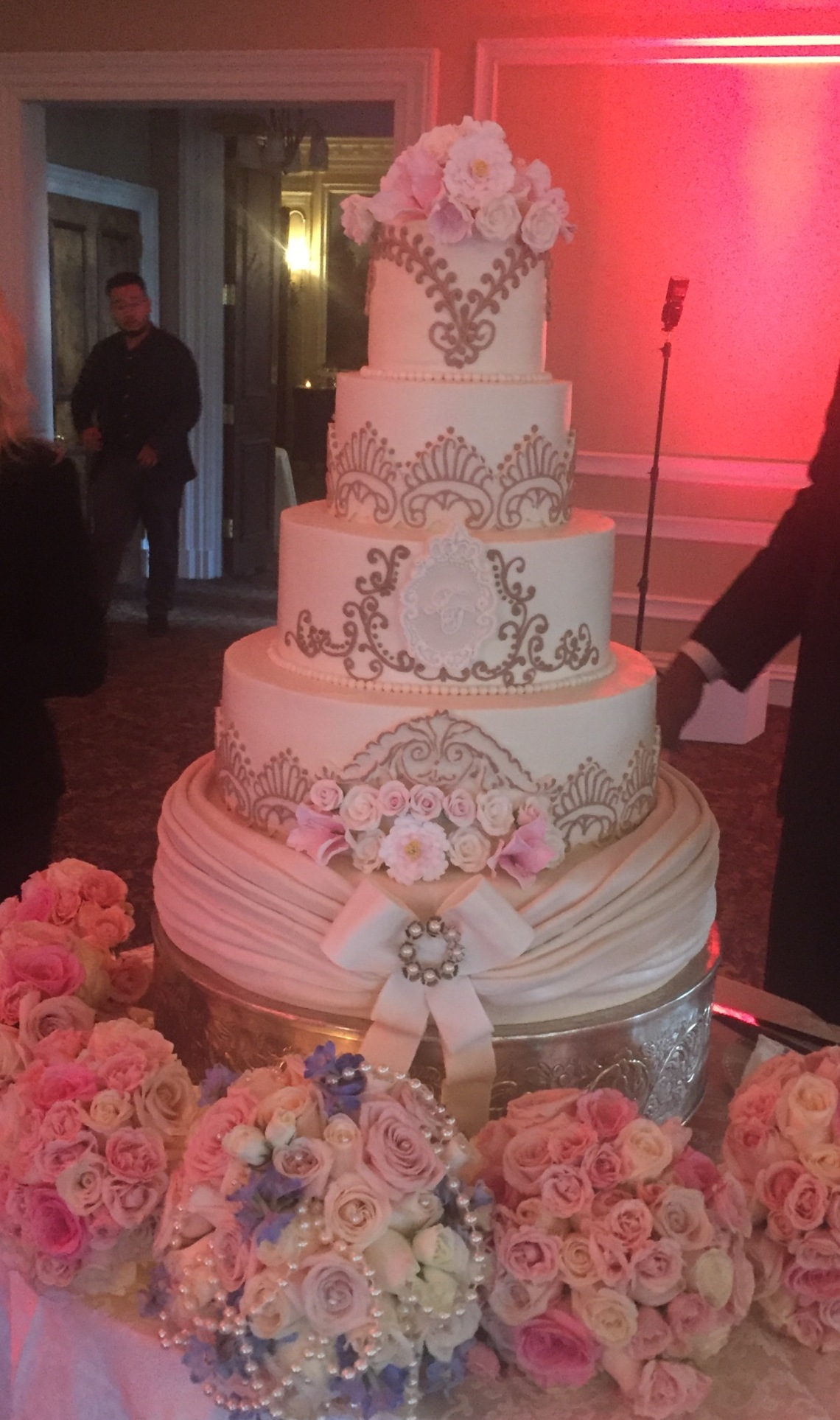Beautiful wedding cake with florist bouquets at Oheka Castle
